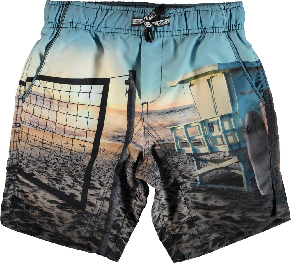 Nario - On The Beach - Swim trunks with beach print.