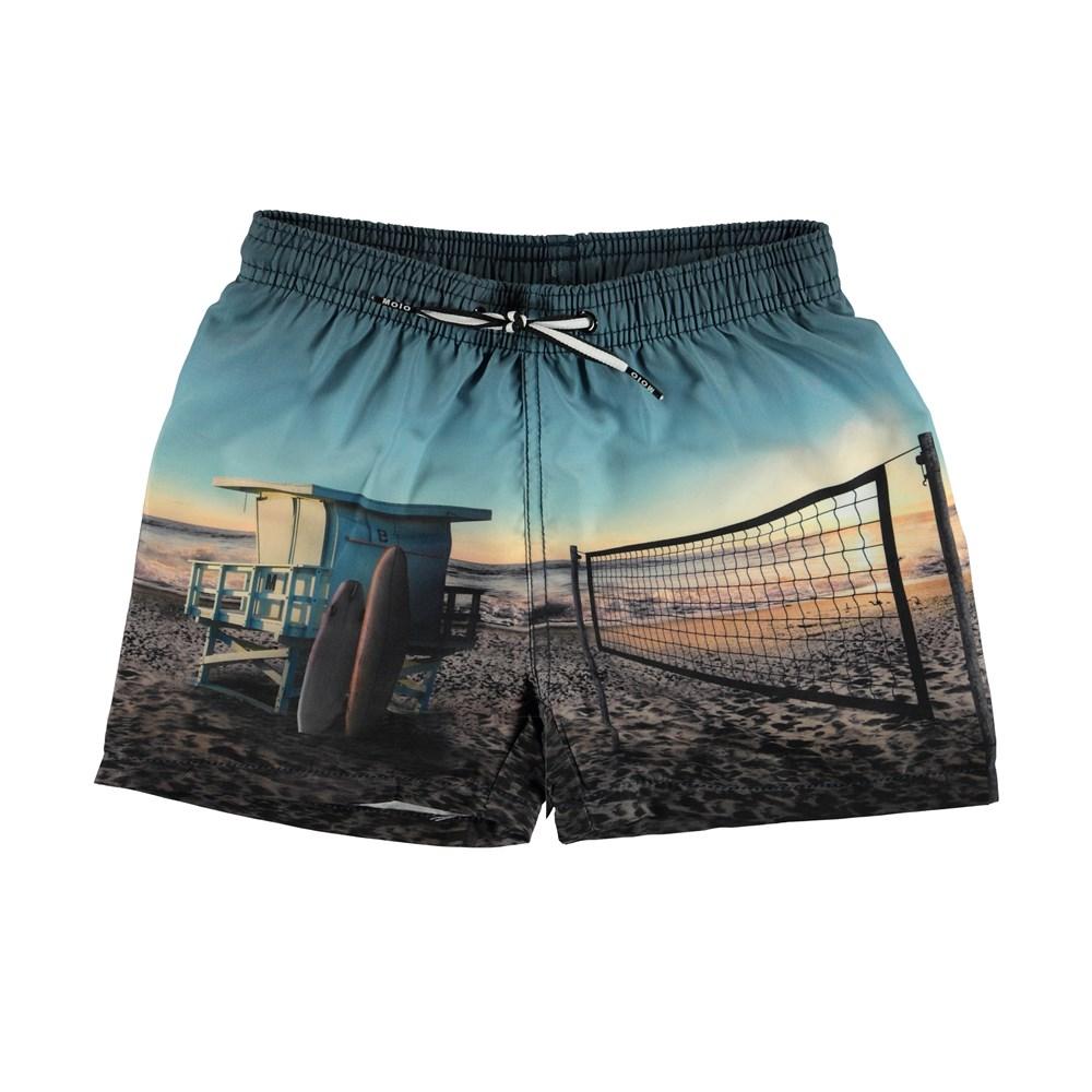Niko - On The Beach - Swim trunks with beach print.