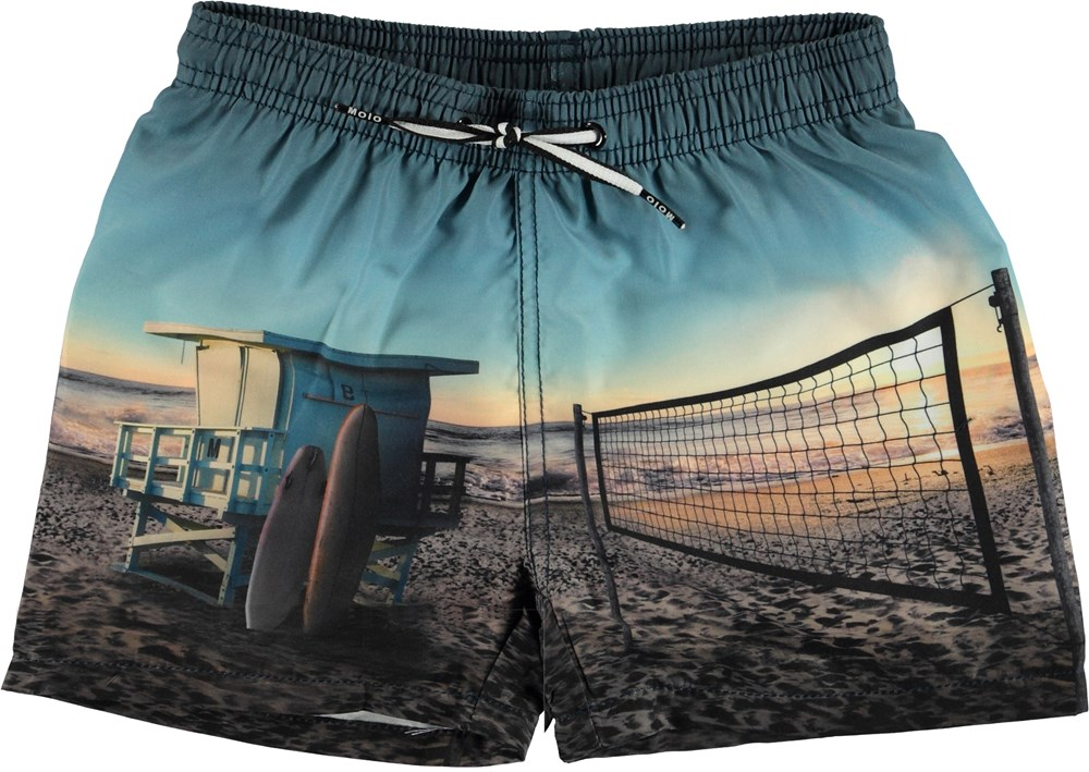 Niko - On The Beach - Swim trunks with beach print.